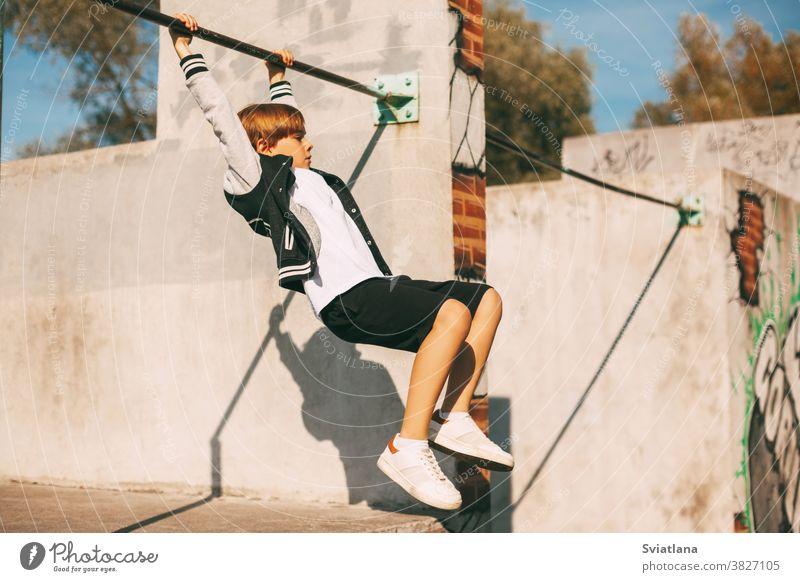 Süßer Junge, der im Park die Hände an der horizontalen Stange hält. Der Junge hängt auf Armeslänge Bar jung Sport Gesundheit stark Übung männlich Training