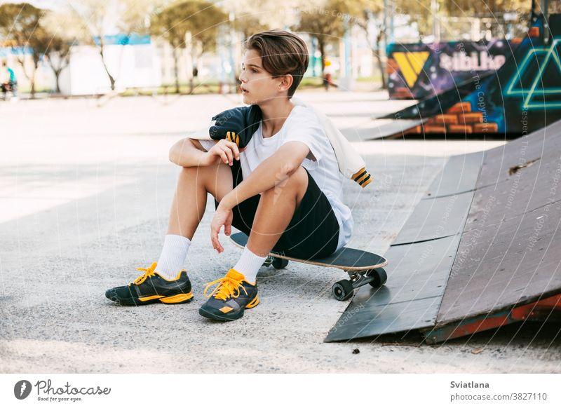 Ein wunderschöner Teenager sitzt auf einem Skateboard in einem speziellen Bereich des Parks. Ein Junge ruht sich nach einer Fahrt in einem Skatepark aus. Aktive Erholung an der frischen Luft