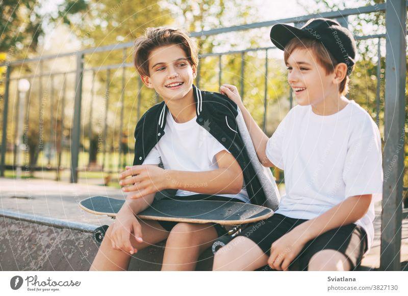 Zwei süße Teenager sitzen in einem Skatepark, entspannen sich nach dem Skateboarden und unterhalten sich. Die Jungs genießen ihre Freizeit im Skatepark, auf der Rampe sitzend. Das Konzept von Jugend, Einheit und Freundschaft