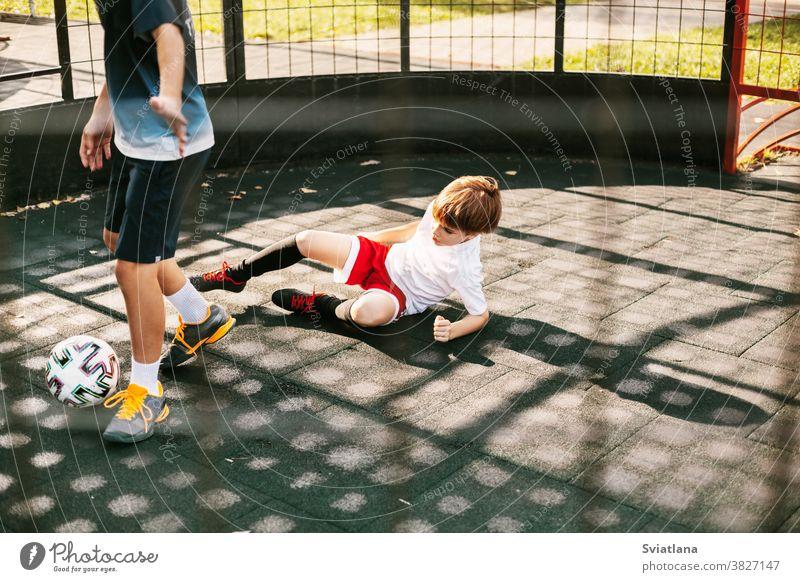 Die Jungen spielen Fußball auf dem Freestyle-Fußballfeld. Die Jungen kämpfen im Spiel um den Ball. Sport, Spiel, Wettbewerb, Fußball-Freistil Spieler Spielen