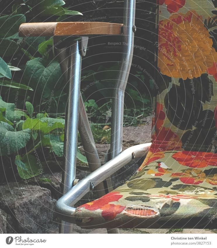 Der alte Campingstuhl mit dem Blumenmuster in gelb, orange und grün hatte schon bessere Zeiten erlebt. retro Retro-Farben Metall Stoffbezug Muster Stuhl