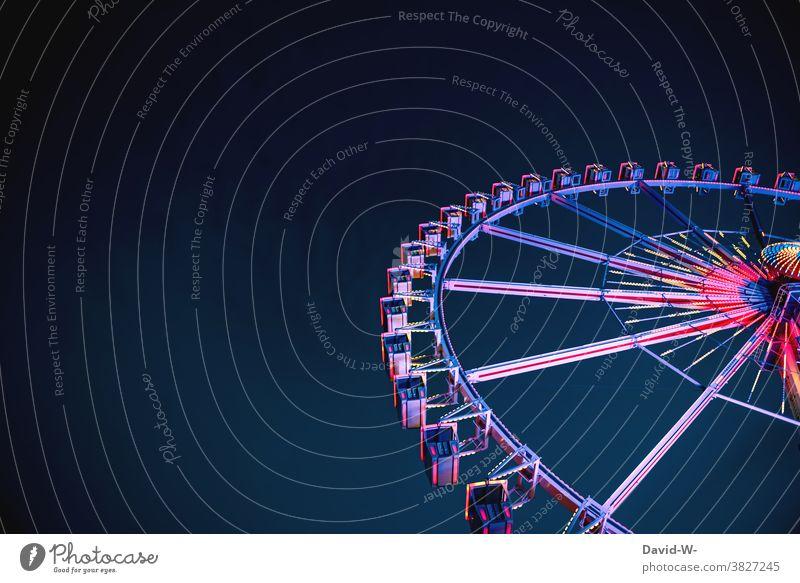 ein leuchtenes Riesenrad am späten Abend ragt in den Himmel empor bunt Kirmes Jahrmarkt freizeit vergnügen Nacht hoch Spaß Aufregung