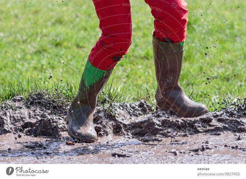 Beine in roter Hose und grünen Gummistiefel springen in einer matschigen Pfütze, so dass der Matsch hochfliegt matschen fliegen Sprung Schlamm spritzen Stiefel