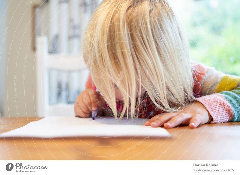 Ein 4-jähriges blondes Mädchen mit einem bunt gestreiften Pullover sitzt an einem Holztisch und zeichnet mit einem violetten Bleistift auf ein weißes Blatt Papier