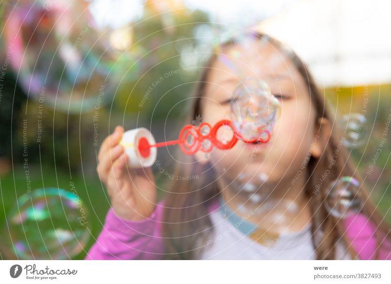 Ein kleines Mädchen macht Seifenblasen im Garten Blasen Kaukasier Kind Kindheit fliegend Fliegen. platzen zerbrechlich Spaß menschlich wenig Spielen s Seife