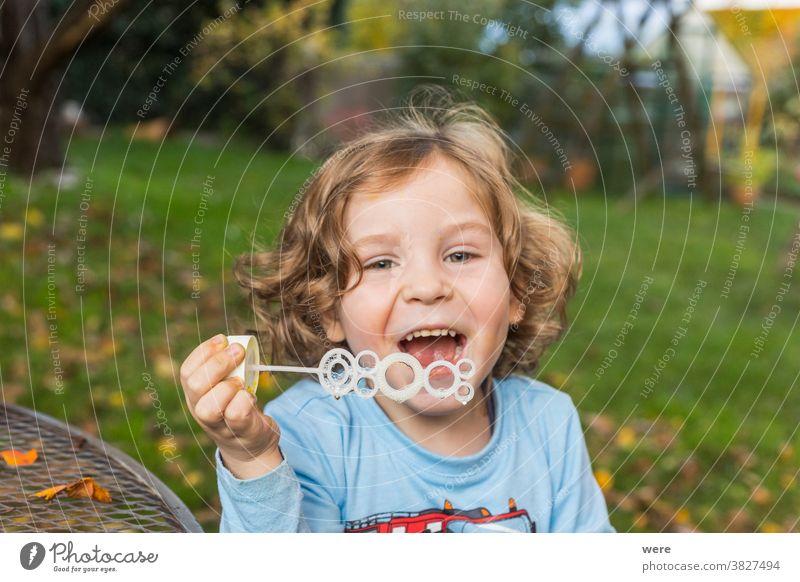 Ein kleiner Junge macht Seifenblasen im Garten Blasen Kaukasier Kind Kindheit fliegend Fliegen. platzen zerbrechlich Spaß menschlich wenig Spielen s Seife