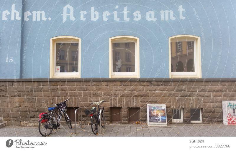 ehemaliges Arbeitsamt früher altdeutsch schrift Beschriftung Witten Fassade Bruchsteinmauerwerk NAtursteinmauer MAuer Fahrrad Stromkasten Grafitti Außenaufnahme