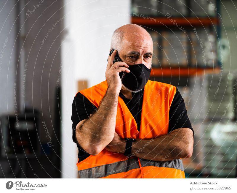 Konzentrierte männliche Lagerarbeiter sprechen auf Smartphone Mann Arbeiter Gespräch Telefonanruf ernst Manager reden Lagerhalle bei der Arbeit Arbeitsplatz