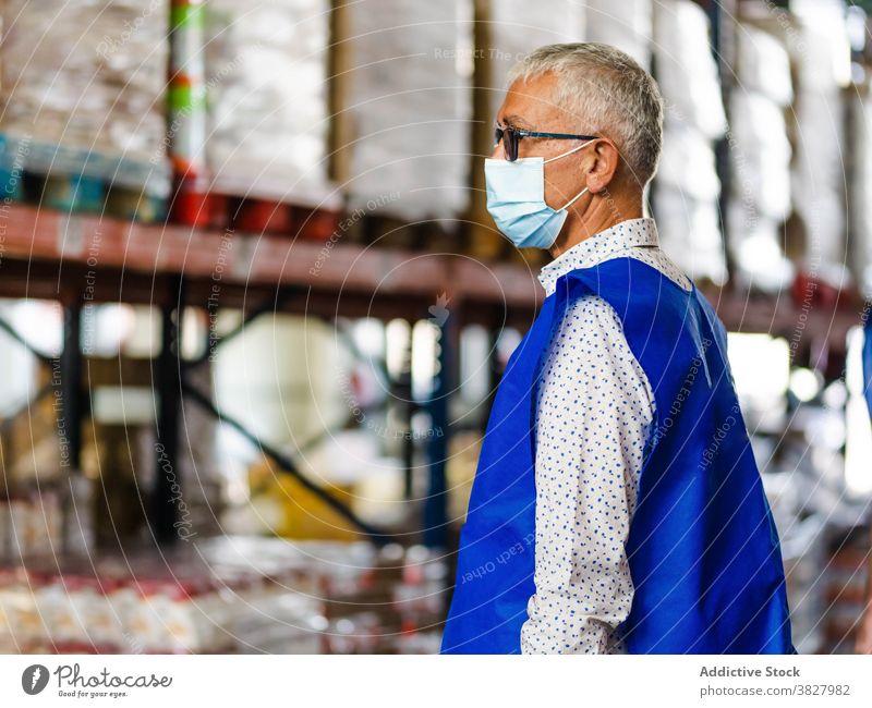 Ruhiger männlicher Arbeiter im Lagerhaus stehend Mann professionell Lagerhalle bei der Arbeit Industrie Uniform Windstille Fokus Speicher industriell