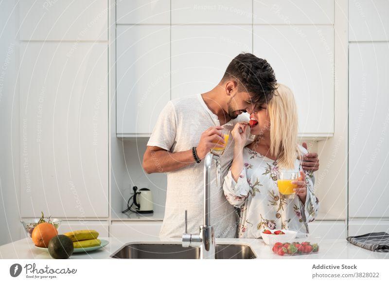 Verliebtes Paar beim Frühstück in moderner Küche Zusammensein Erdbeeren essen genießen Morgen Umarmung Liebe früh frisch orange Saft Lebensmittel Frucht