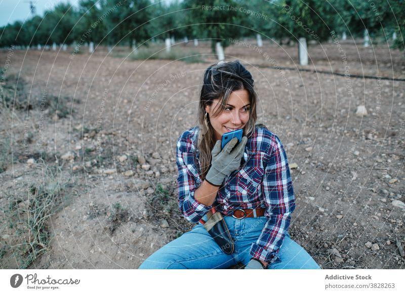 Frau benutzt Smartphone auf dem Bauernhof Landwirt sich[Akk] entspannen Arbeiter Aufzeichnen Audio Stimme Nachricht Telefon Mobile online Browsen Boden