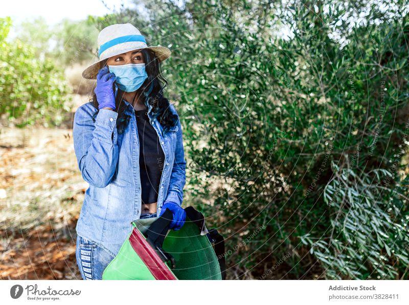 Junge Frau in medizinischer Maske, die während der Ernte auf dem Smartphone spricht Telefonanruf Mundschutz COVID Gespräch benutzend Garten reden behüten