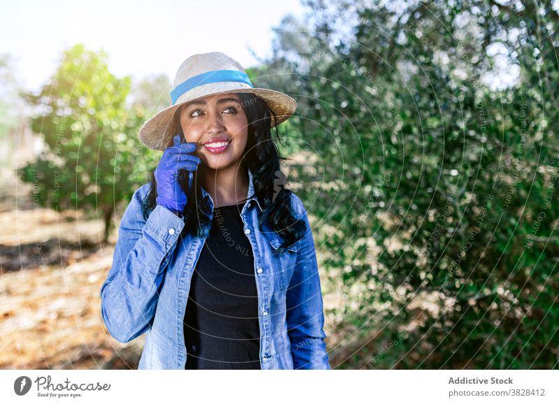 Junge Frau spricht am Telefon, während sie im Garten steht sprechend benutzend positiv Arbeit Obstgarten Ernte Frucht Bauernhof Anschluss Mitteilung digital