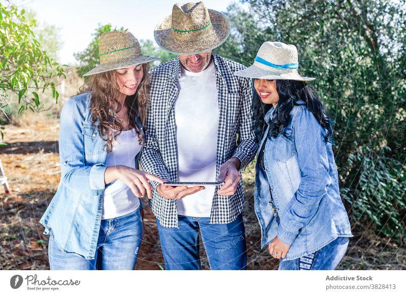 Lächelnde Kollegen mit Tablet im grünen Garten Mann Frauen Menschengruppe Ernte benutzend Tablette Bauernhof kultivieren Ackerbau Apparatur professionell