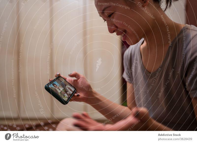 Asiatische Frau macht Videoanruf auf Smartphone zu Hause Coronavirus Selbstisolierung soziale Distanzierung Kommunizieren Video-Chat sitzen online Sitzung