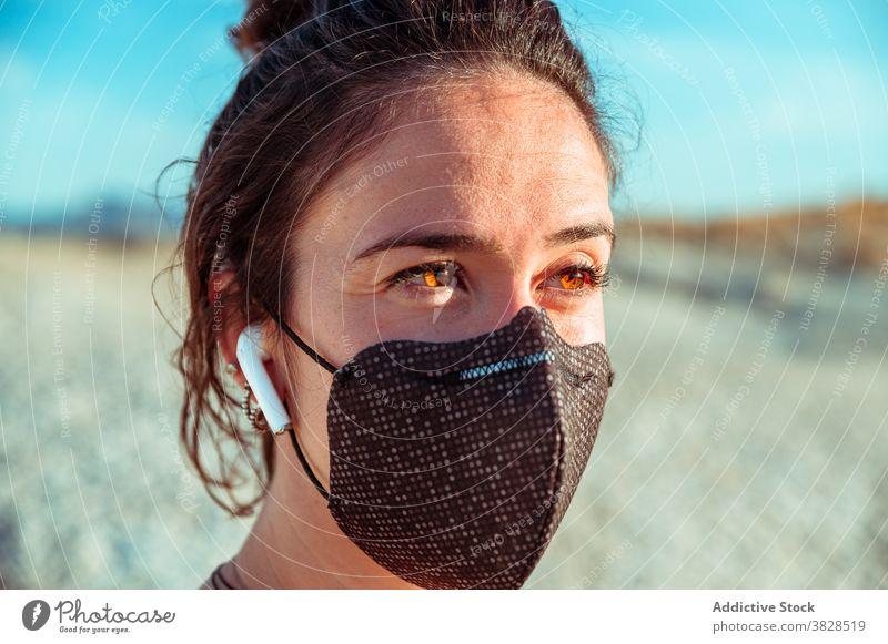 Sportliche Frau mit Maske und Kopfhörern inmitten von trockenem Terrain Sportlerin Mundschutz Ohrstöpsel wüst selbstbewusst zuhören behüten Drahtlos stark