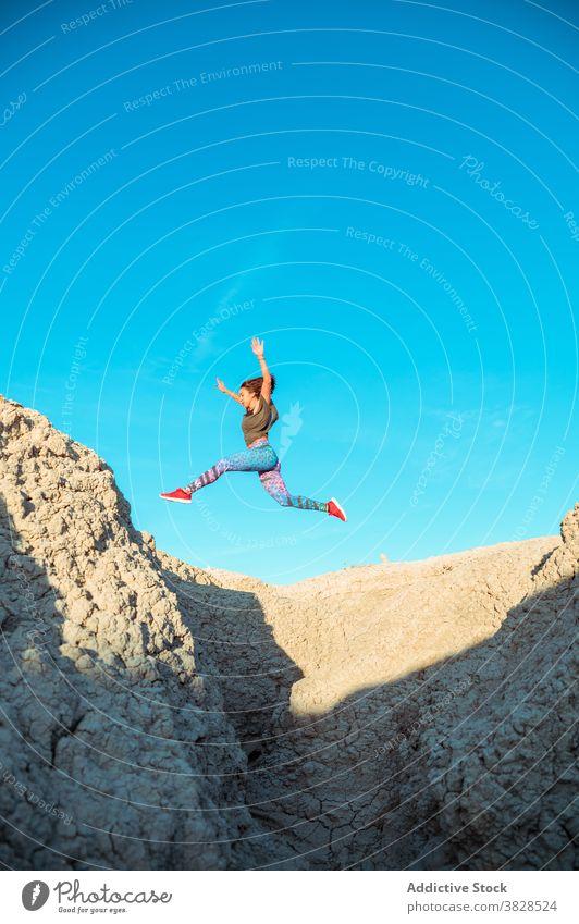 Starke Sportlerin springt über sandigen Hügel springen Fliege Skyline Blauer Himmel wüst rau aktiv Energie Sprung Athlet Frau Berghang Gelände Natur Training