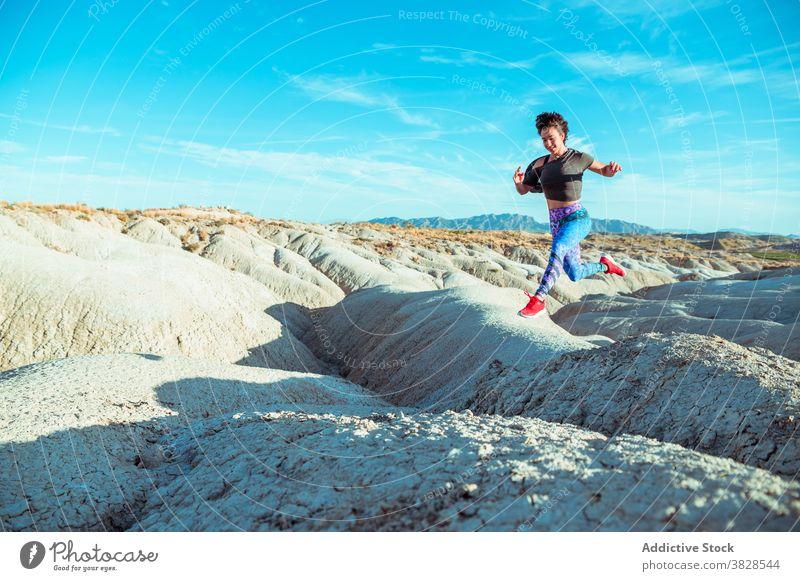 Energetische Sportlerin beim Laufen in der Wüste auf hügeligem Terrain laufen springen wüst rau Ödland aktiv felsig Energie Athlet Frau Berghang Gelände Natur