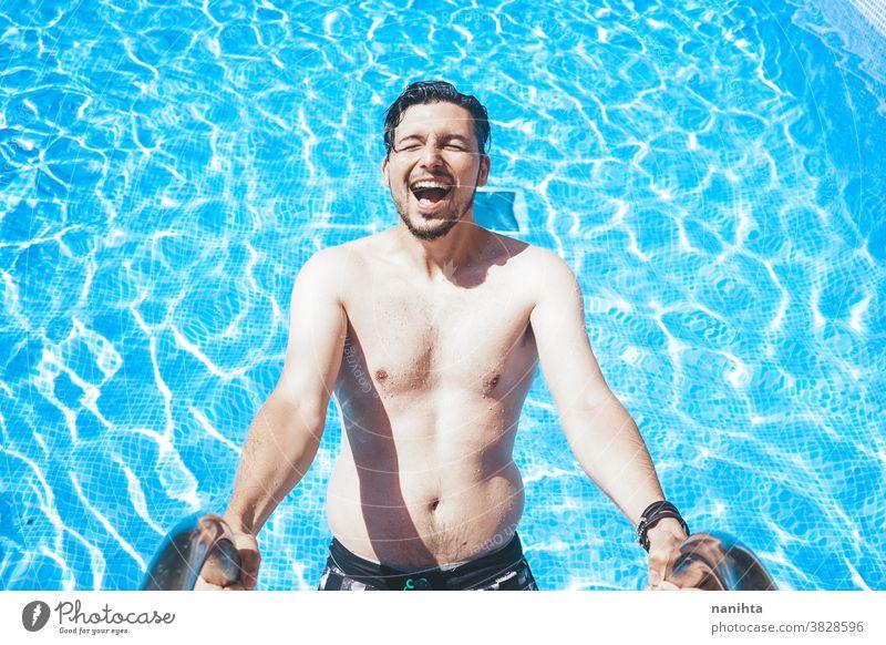 Junger, gutaussehender Mann posiert in der Nähe eines Pools attraktiv sexy männlich Schwimmbad Sommer Haut Vollbart Typ Lächeln Bräune blau Wasser Party Porträt