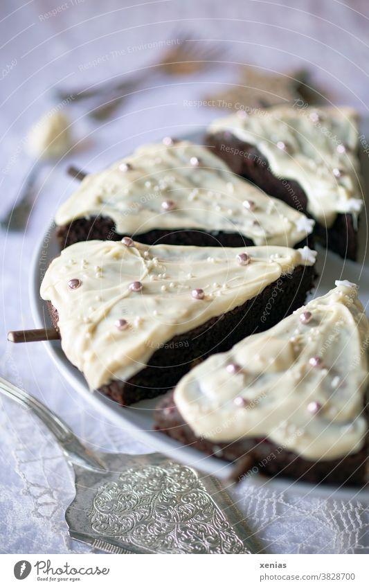 Vier Stück weihnachtlich dekorierter Schokoladenkuchen in Tannenbaumform mit weißer Schokolade überzogen liegen auf einem weißen Teller stehend auf einer Spitzendecke