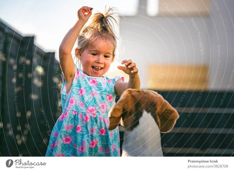 Kleines Mädchen rennt mit einem Beagle-Hund im Garten an einem Sommertag. Konzept Haustier mit Kindern. Baby Zusammengehörigkeitsgefühl 2-3 Familie Leckerbissen