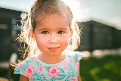 Wunderschönes Porträt eines kleinen Mädchens in einem sonnigen, grünen Hof im Sommer. Baby Kindheit Hintergrund 2-3 happines bezaubernd niedlich Natur