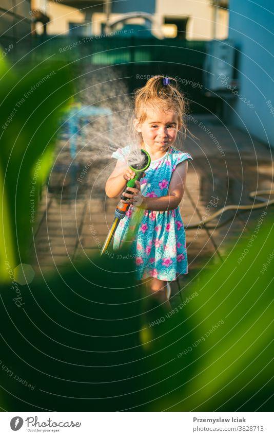 Glückliches 2-3-jähriges Mädchen mit Gartenschlauch gießt die Pflanzen. Baby Wattering Hinterhof Familie Wasser Liebe Kind Person Sommer Natur Sonne Tier