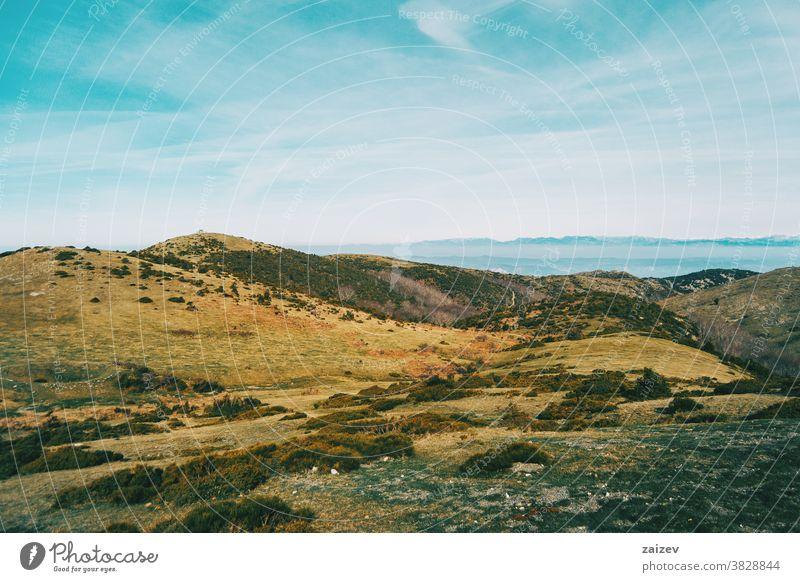 Blick auf eine Landschaft mit einigen gelblichen Hügeln Berge wild Umwelt Natur Vegetation Sträucher grün Gelblich braun Himmel Boden Hintergrund Bäume