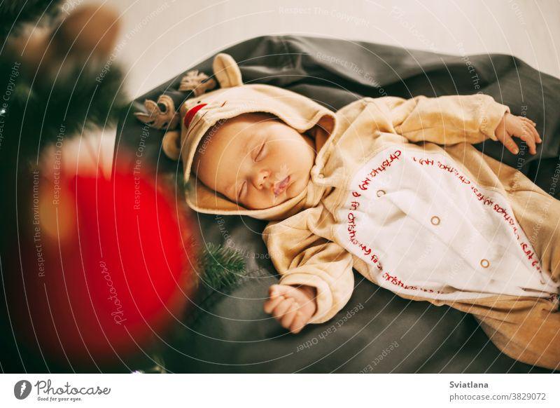 Ein süßer neugeborener Junge in einem Rentierkostüm schläft auf einem Puff in einem für Weihnachten und Neujahr geschmückten Zimmer. Ein Kind schläft am Silvesterabend neben einem Weihnachtsbaum. Das Konzept von Weihnachten und Neujahr. Feier, Dekoration, Grußkarte, ...