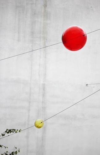 Kinderbelustigung Mauer Wand Glaskugel Drahtseil hängen außergewöhnlich rund gelb grau rot Freude Partnerschaft Design Idee Konzentration Leichtigkeit Netzwerk