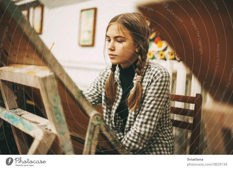 Hübsches Teenagermädchen an der Kunstschule malt an der Staffelei, Kreativitätskonzept, Kunstatelier Atelier Frau Palette Bürste Schule Menschen Konzept Malerei