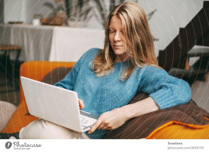 Junge Frau benutzt Laptop, checkt online auf dem Sofa sitzend E-Mail-Nachrichten. Hübsches Mädchen arbeitet am Computer, sieht sich ein Webinar an, lernt zu Hause