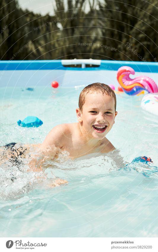 Porträt eines glücklich lächelnden Jungen, der an einem sonnigen Sommertag im Schwimmbad spielt und Spaß hat authentisch Hinterhof Kindheit Kinder Familie