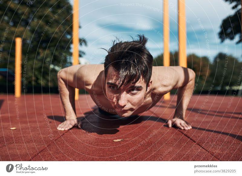 Junger hemdloser Bodybuilder macht Liegestützen auf rotem Gummiboden während seines Trainings in einem modernen Gymnastikpark calisthenics Pflege Kaukasier