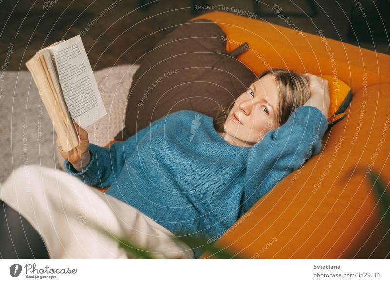 Ein schönes Mädchen entspannt sich auf dem Sofa im Wohnzimmer und liest ihren Lieblingsroman. Ein süßes, nachdenkliches Mädchen liegt auf dem Sofa und liest ein Buch. Online arbeiten, freiberuflich tätig, soziale Distanz