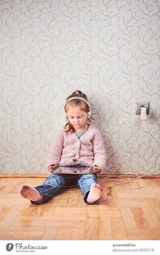 Kleines Mädchen im Vorschulalter lernt online Rätsel lösen und spielt zu Hause Lernspiele auf Tablet Aufmerksamkeit Bett Schlafzimmer Kaukasier Kind Kindheit