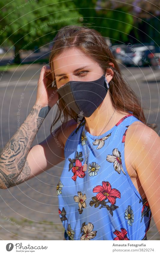 Frau im Freien bei der Geburt eines Huhns mit Maske COVID Alkohol Pandemie Mundschutz Entfernung Protokoll neue Normale Kleid hübsch Mädchen Straße Porträt