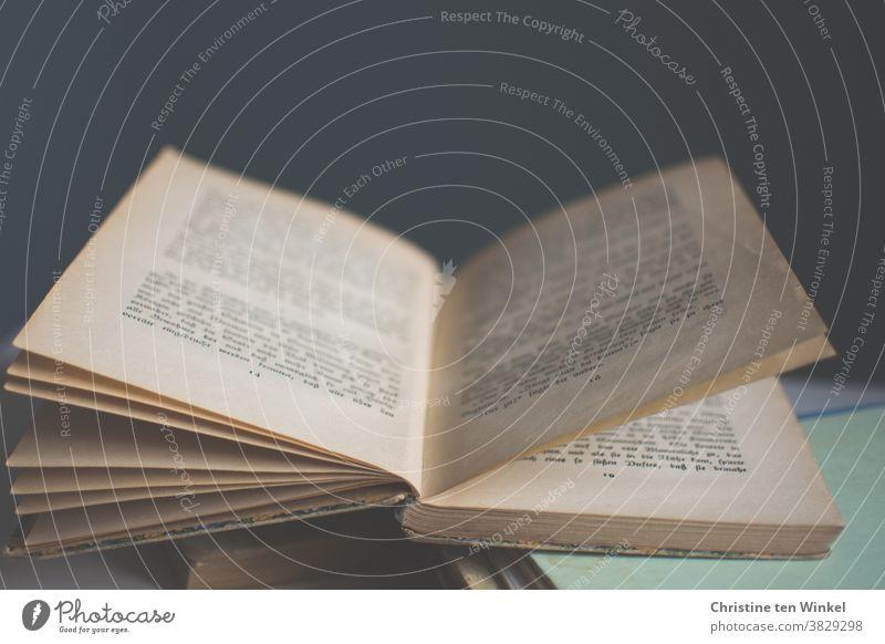 Zeit für ein gutes Buch...  Aufgeschlagenes älteres Buch liegt auf mehreren Büchern. Schwache Tiefenschärfe und dunkler Hintergrund. Bücherstapel Lesestoff