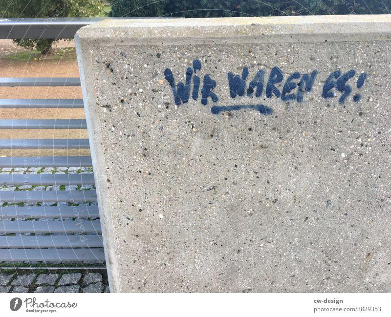 WIR WAREN ES! Graffiti Schmiererei Betonwand blau Schriftzeichen Wand Mauer Außenaufnahme Menschenleer Tag Wort Text Buchstaben Fassade Straßenkunst