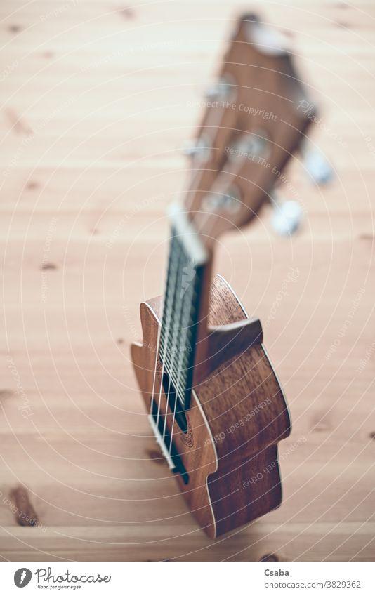 Eine braune Sopran-Ukulele auf Holzgrund hölzern akustisch Instrument vertikal Objekt Musical hawaiianisch Gitarre Schnur Hintergrund Musik Rosette Kunst