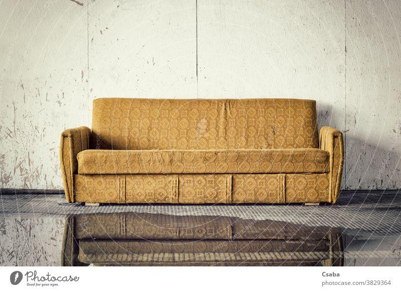 Ausrangiertes altes braunes Sofa gegen schmutzige Wand Liege Möbel abgeworfen ruiniert dreckig verwendet gelb Straße im Freien Müll Trödel gebrochen Wasser