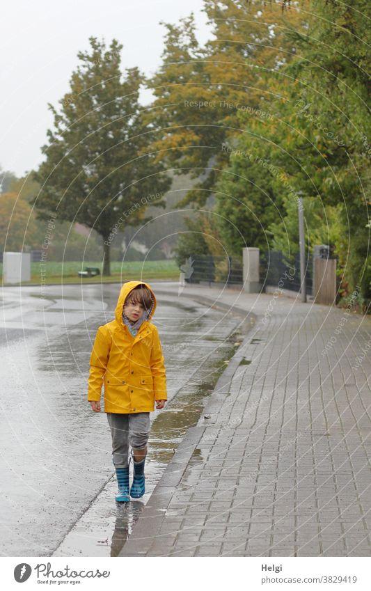 Regenspaziergang - Junge in gelber Regenjacke und Gummistiefeln läuft am Straßenrand durch Pfützen Mensch Kind Fußweg Dorf Baum Natur Regenwetter Umwelt