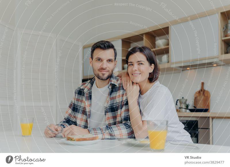 Positive brünette Frau lehnt sich an die Schulter ihres Mannes, posieren gemeinsam in der Küche, genießen köstliches Frühstück, haben glückliche Stimmung, schauen direkt in die Kamera, haben gute Beziehungen. Familienkonzept