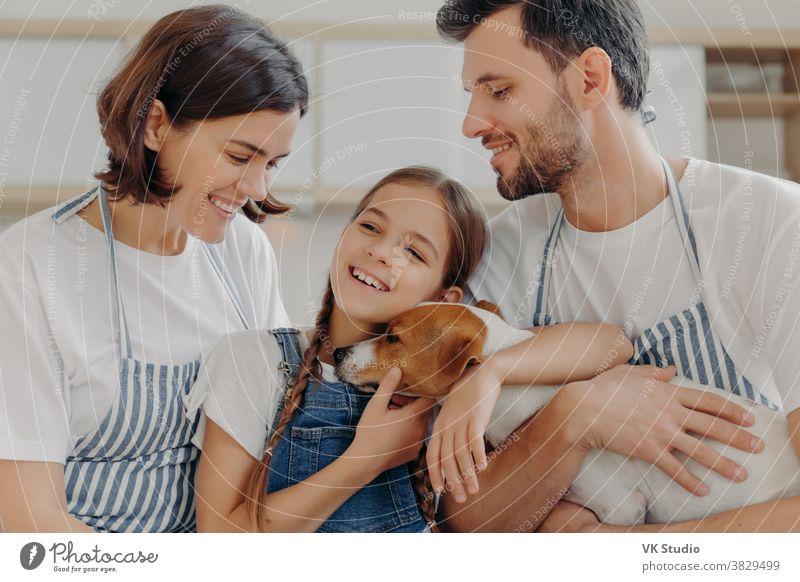 Eine glückliche, nette Familie lächelt und drückt aufrichtige Emotionen aus, genießt die gemeinsame Zeit in einem gemütlichen Zuhause. Lächelndes kleines Kind froh, dass Eltern ihr neues Haustier, den knuddelnden Jack Russell Terrier, mit Liebe und Fürsorge gekauft haben.