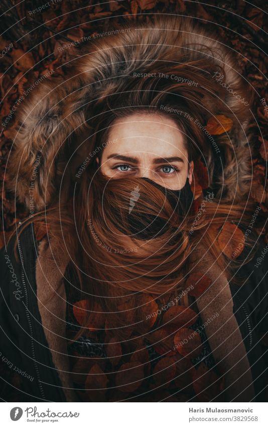 Schöne Frau im Herbstlaub liegend mit Gesichtsmaske Herbstfarben Herbst-Vibes Hintergrund schön schöne Frau Kaukasier Feier Sauberkeit Kleidung Bekleidung