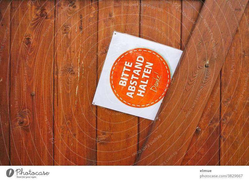 """Schild mit der Aufschrift """"BITTE ABSTAND HALTEN - Danke!"""" klemmt schräg an einer braunen Holztür Bitte Abstand halten Sicherheitsabstand schützen klemmen"""