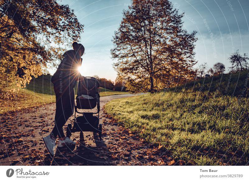 Na wer ist denn da wach?! Mutter schaut während eines Herbstspaziergangs in den Kinderwagen. Szene vor Gegenlicht, die Sonnenstrahlen umspielen die junge Mutter