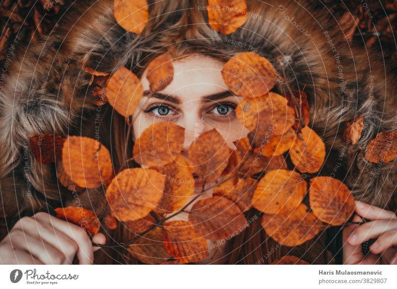 Frau hält Herbstblätter als natürliche Gesichtsmaske Herbstfarben Herbstlaub Herbst-Vibes Hintergrund schön schöne Frau Kaukasier Feier Sauberkeit abschließen
