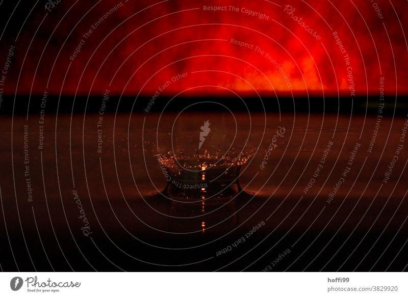 ein Tropfen fällt in ein Gefäß mit Wasser - rote Glut schimmert am Horizont roter hintergrund Blutrot feuer feuerrot tropfenbild Makroaufnahme Farbe nass