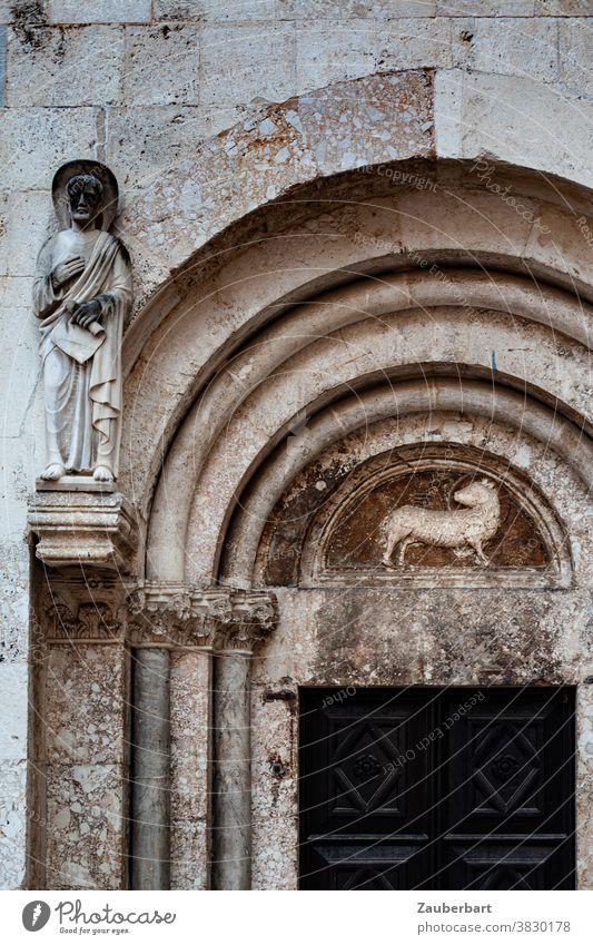 Lamm als Relief und Statue eines Heiligen an einem romanischen Kirchenportal mit Rundbogen Heiliger Portal alt Religion religiös Verehrung Religion & Glaube